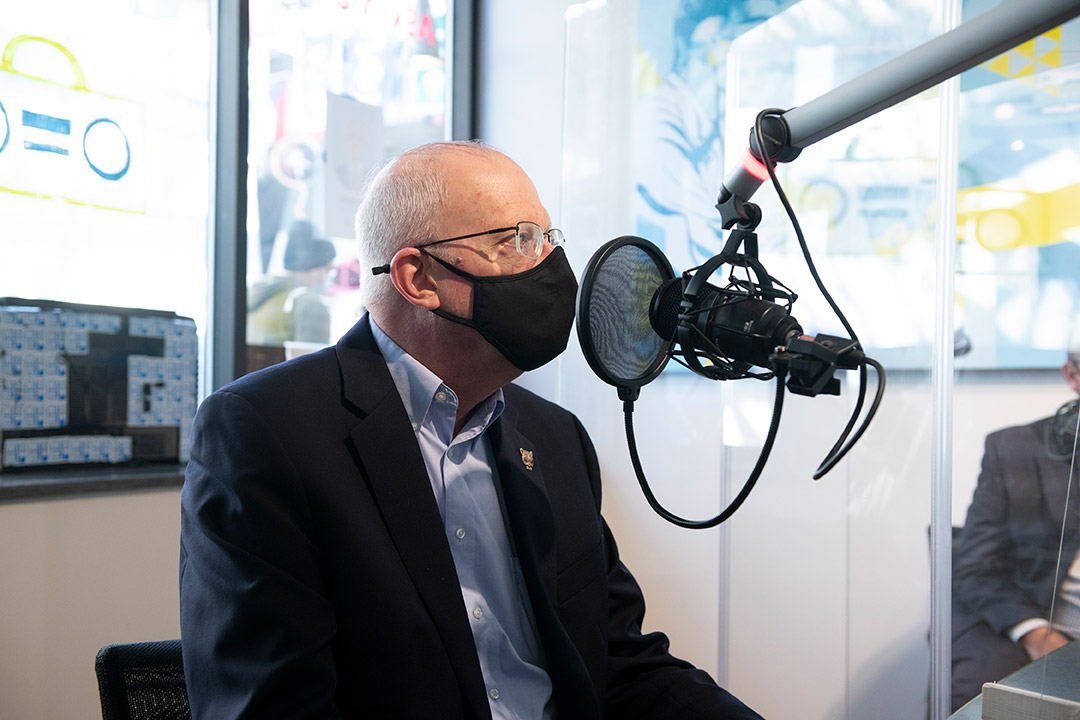 President Munson wearing a mask talking into a radio station microphone.