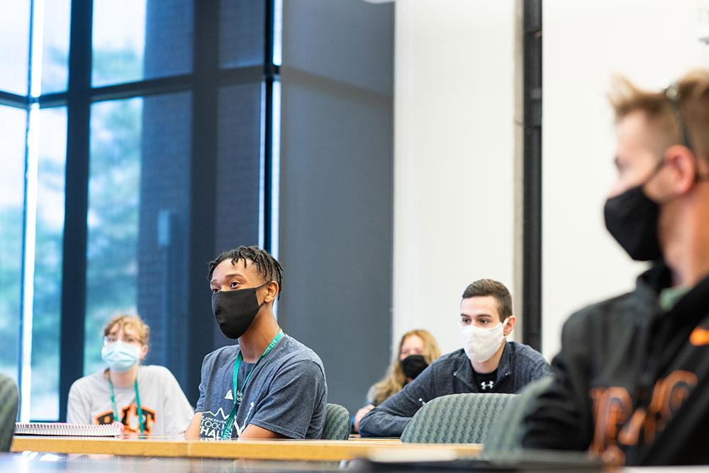 students wearing face masks and sitting socially distanced in a classroom setting.