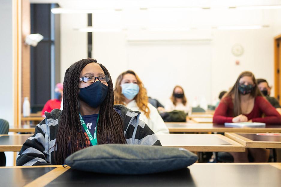 students wearing masks sitting at tables.
