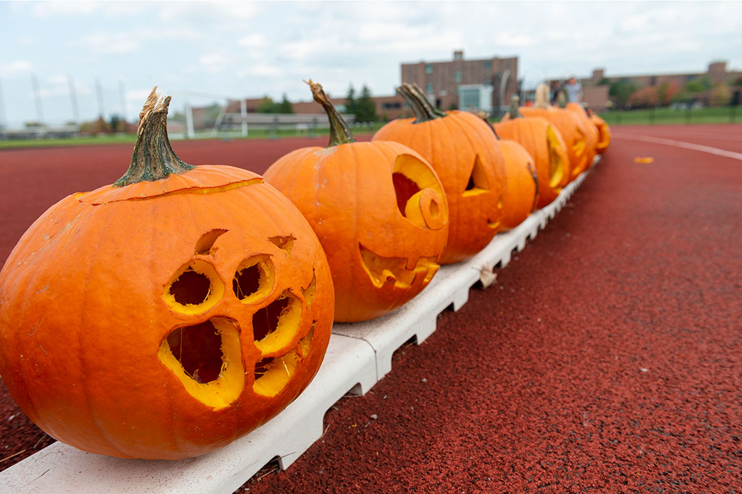 jack-o-lanterns lined up along an outdoor track.