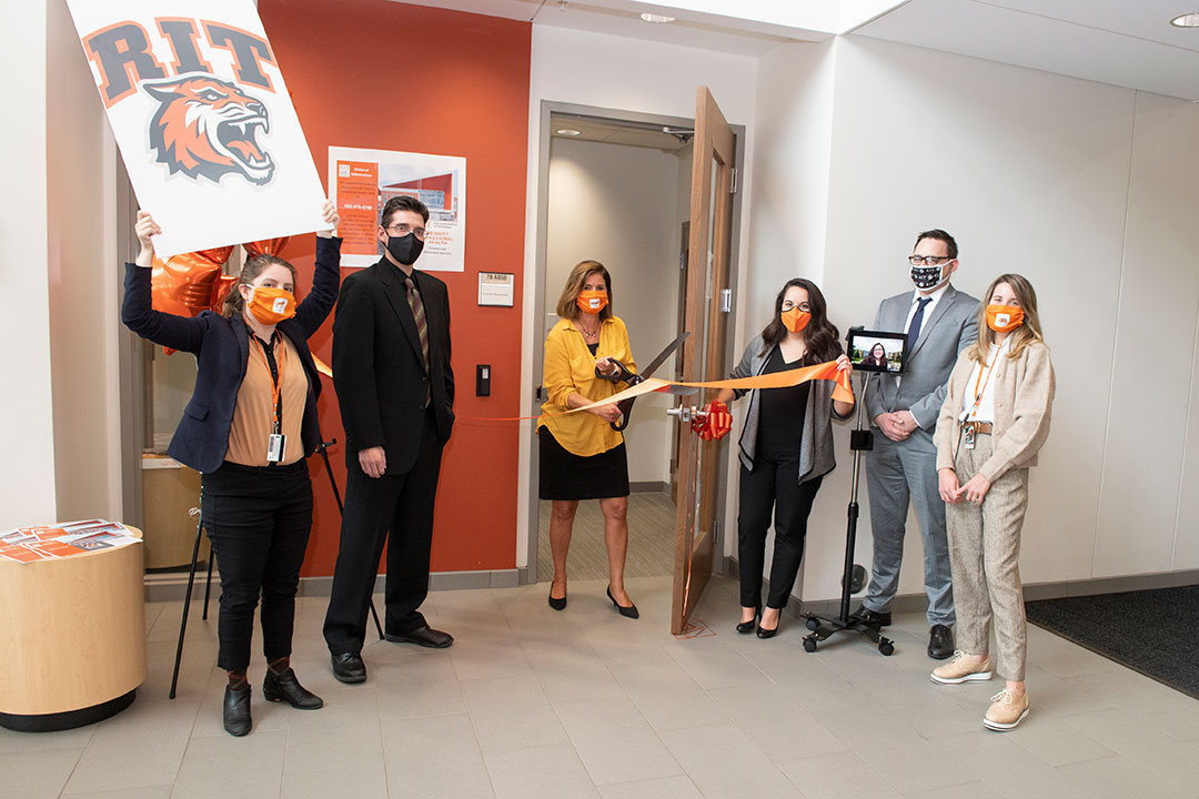 six people celebrate opening of a clinic by cutting a ribbon with oversized scissors.