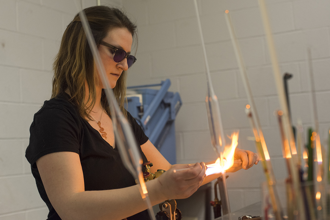 Madeline Rile Smith works in the flame working studio.