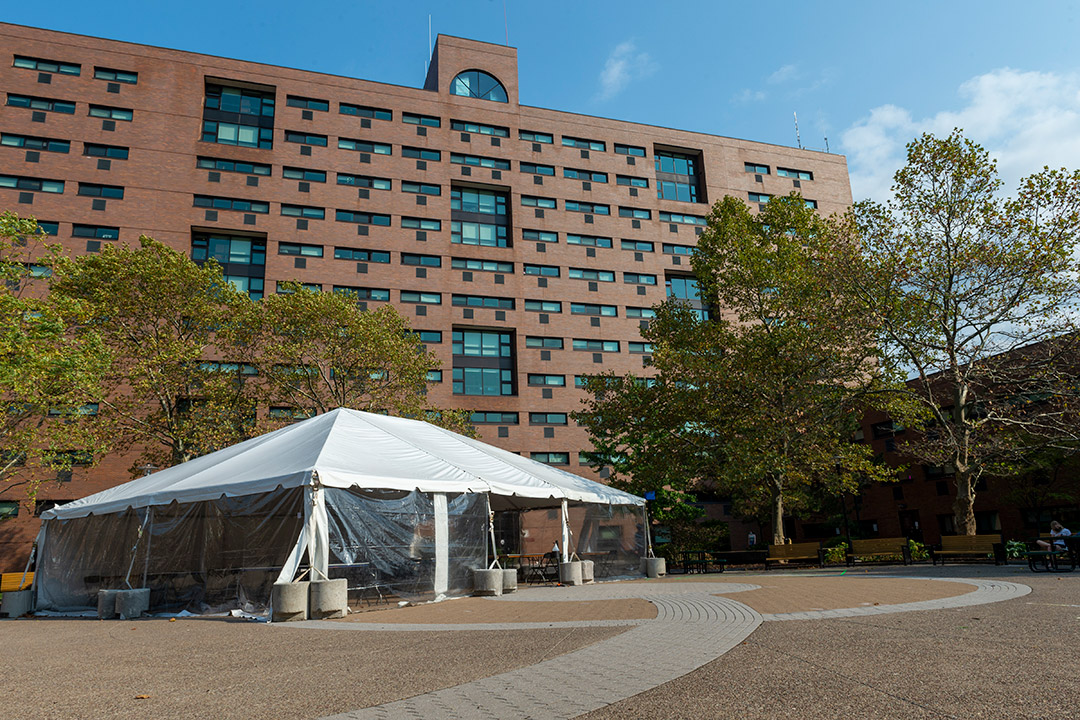 party tent set up outside of brick building.