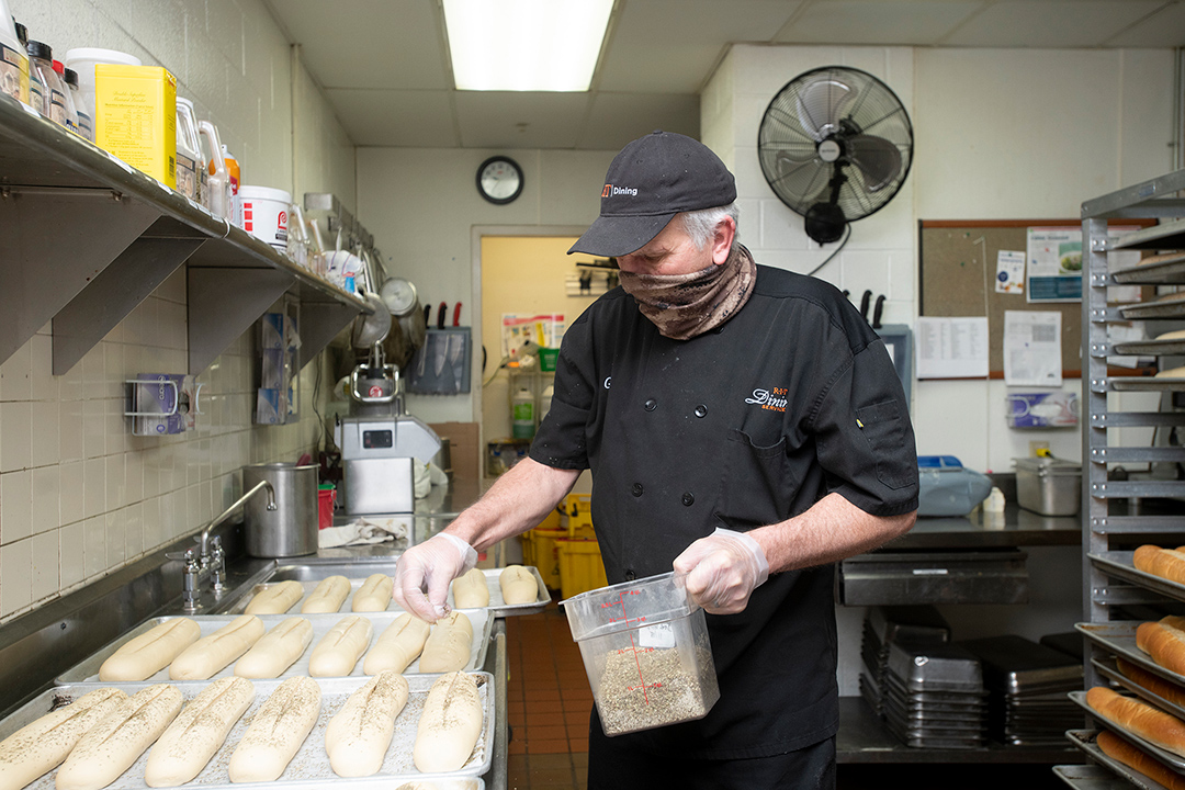 food service worker sprinkling sesame seeds onto loaves of bread dough.