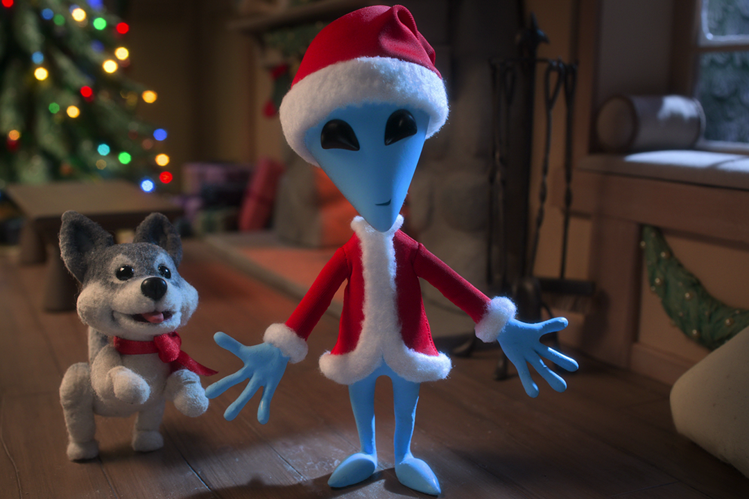 An animated alien dressed in a Santa suit.