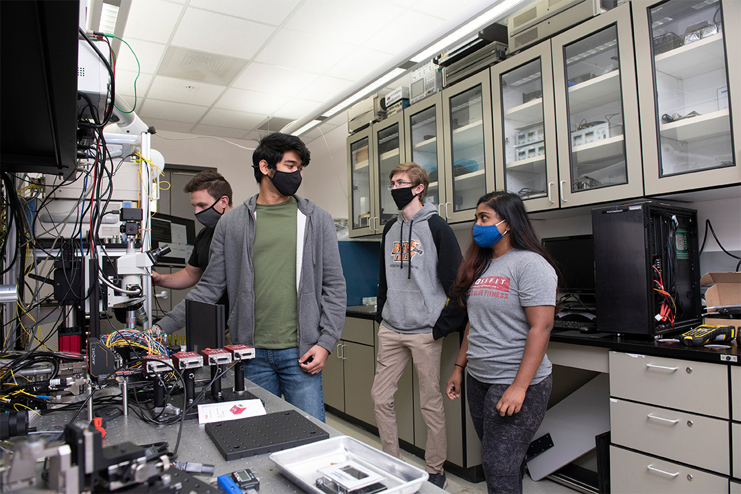 four student researchers wearing masks in a quantum research lab.