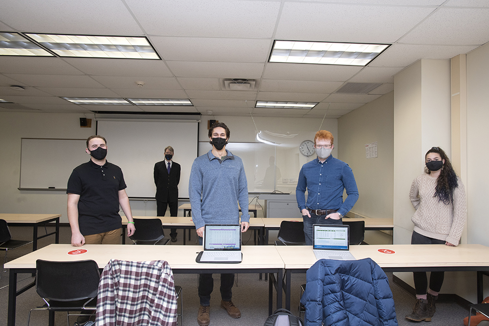 students and staff standing in masks behind table with computers.