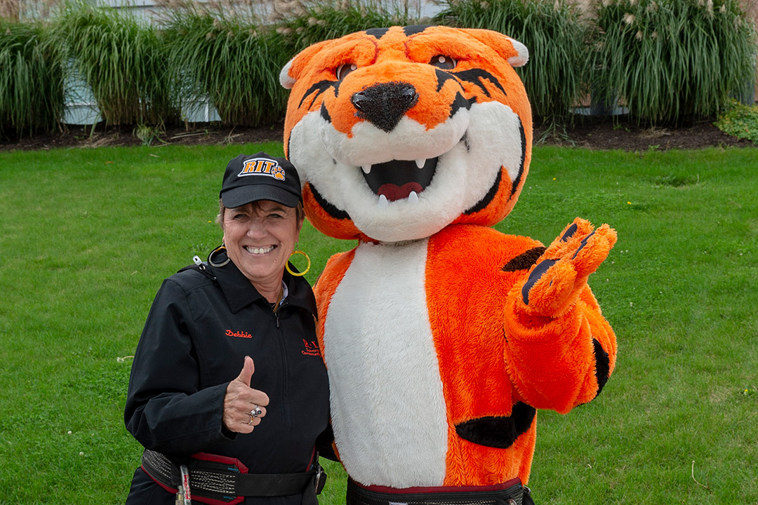 woman posing with tiger mascot.