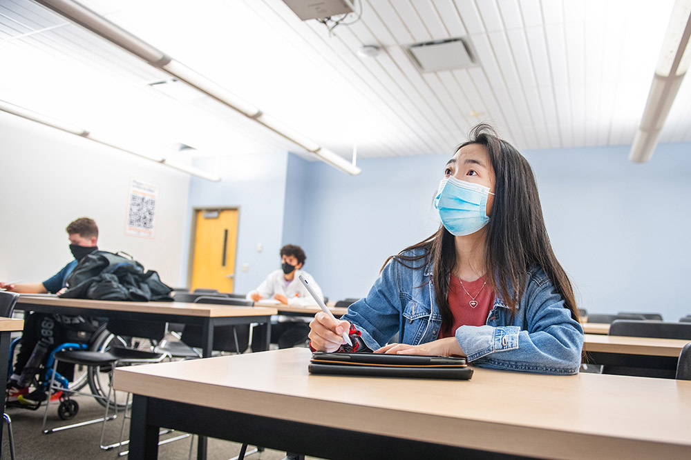 students wearing face masks and sitting one to a table in a classroom.