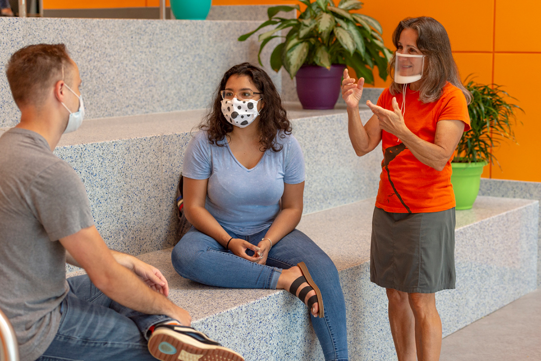 three people wearing face masks and one person using sign language.
