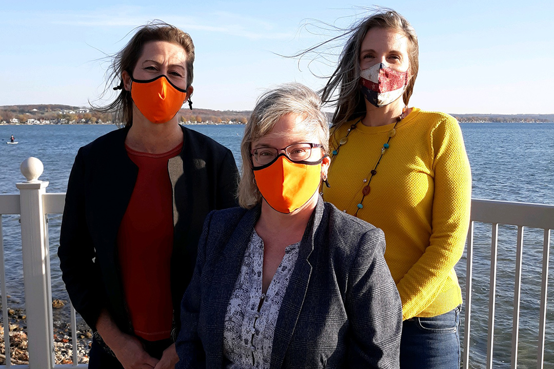 three women wearing fask masks standing on deck near a body of water.