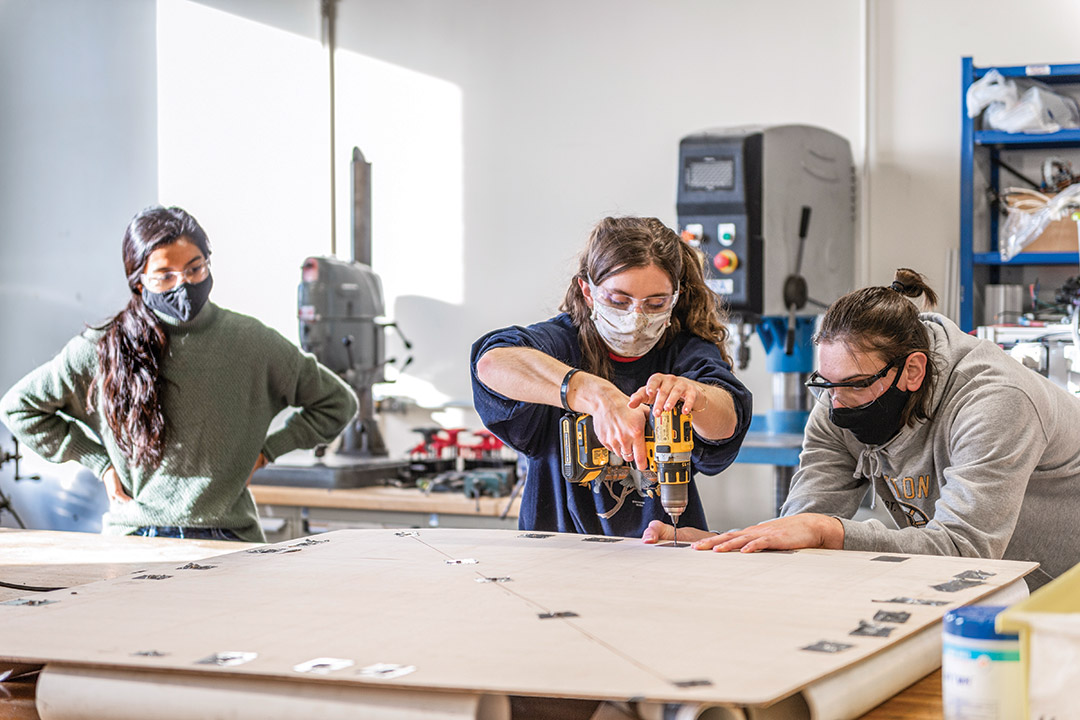 three students wearing masks and working with power tools.