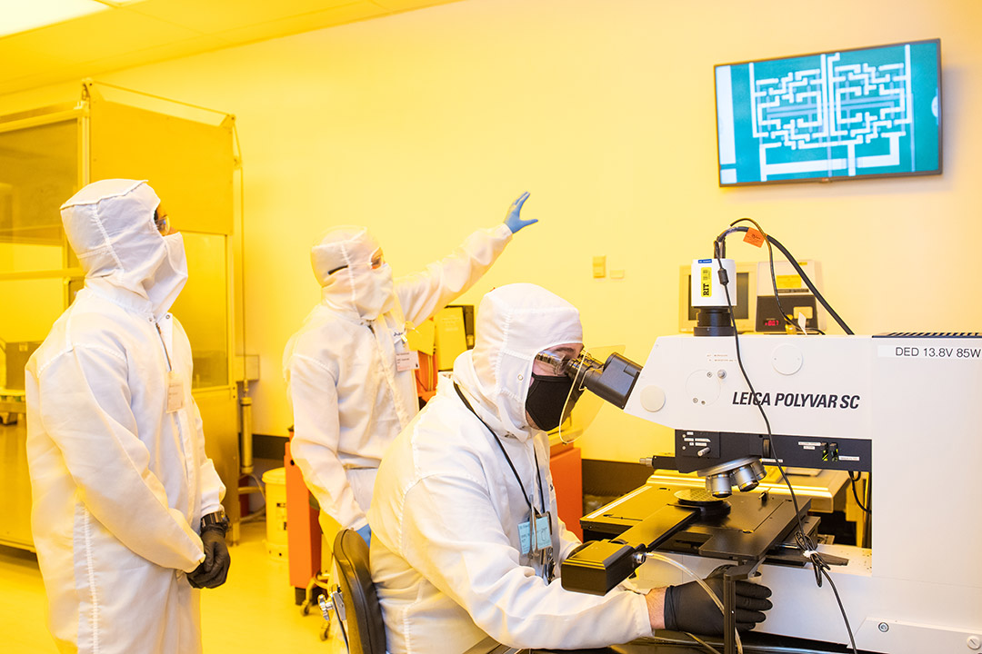 researchers wearing clean suits analyzing a magnified view of an integrated circuit.