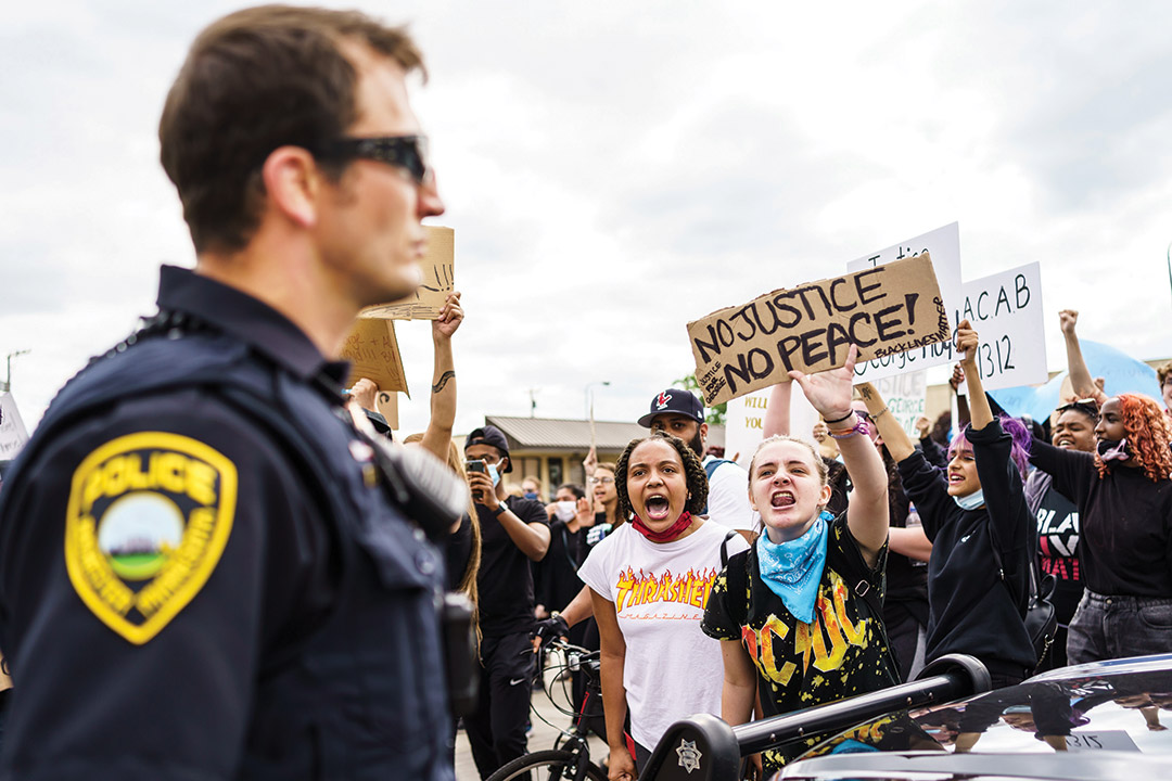 two young girls in a crowd yelling at a police officer during a protest.