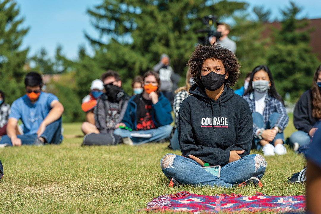students wearing face masks and sitting socially distanced on a lawn.