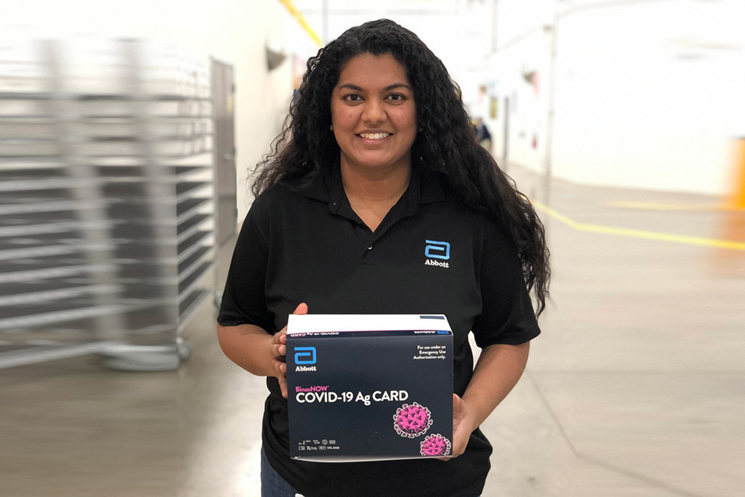 woman holding box of COVID-19 rapid tests.