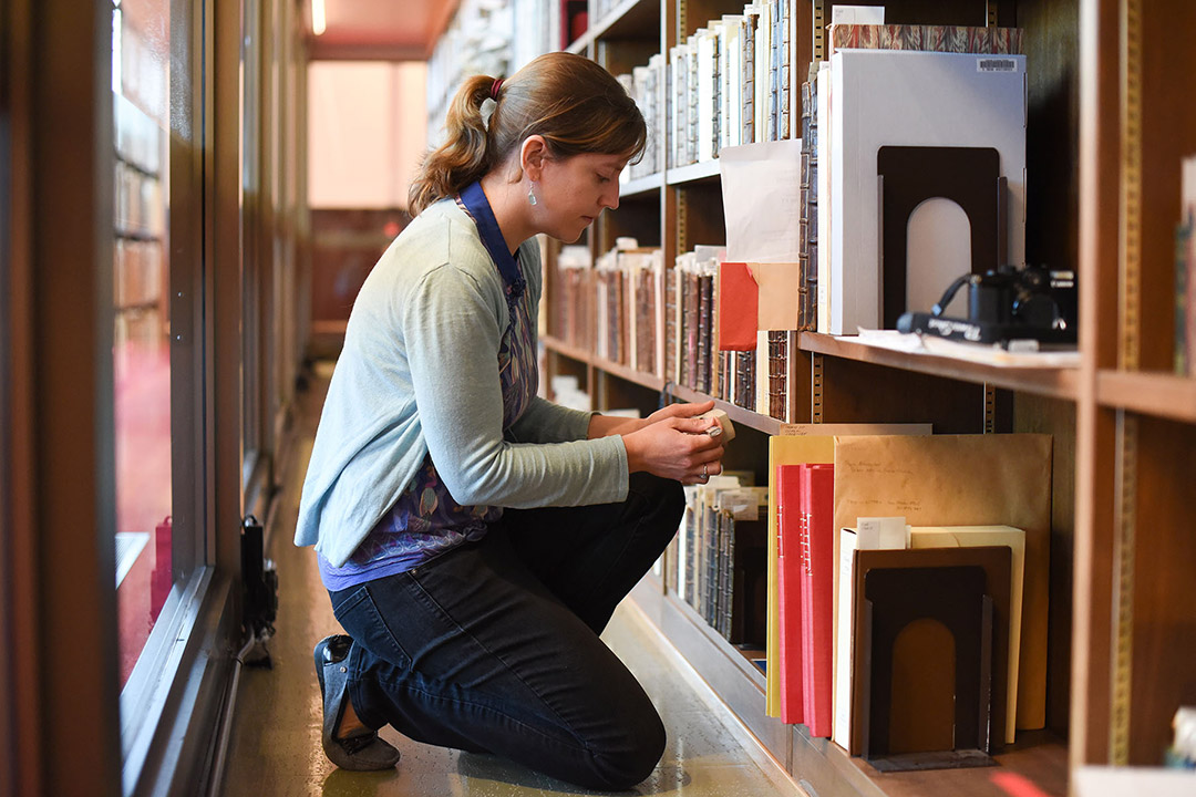 researcher examining row of books in a library.