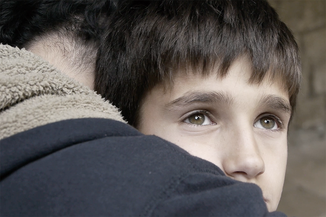 A boy looks off into the distance as he is embraced.