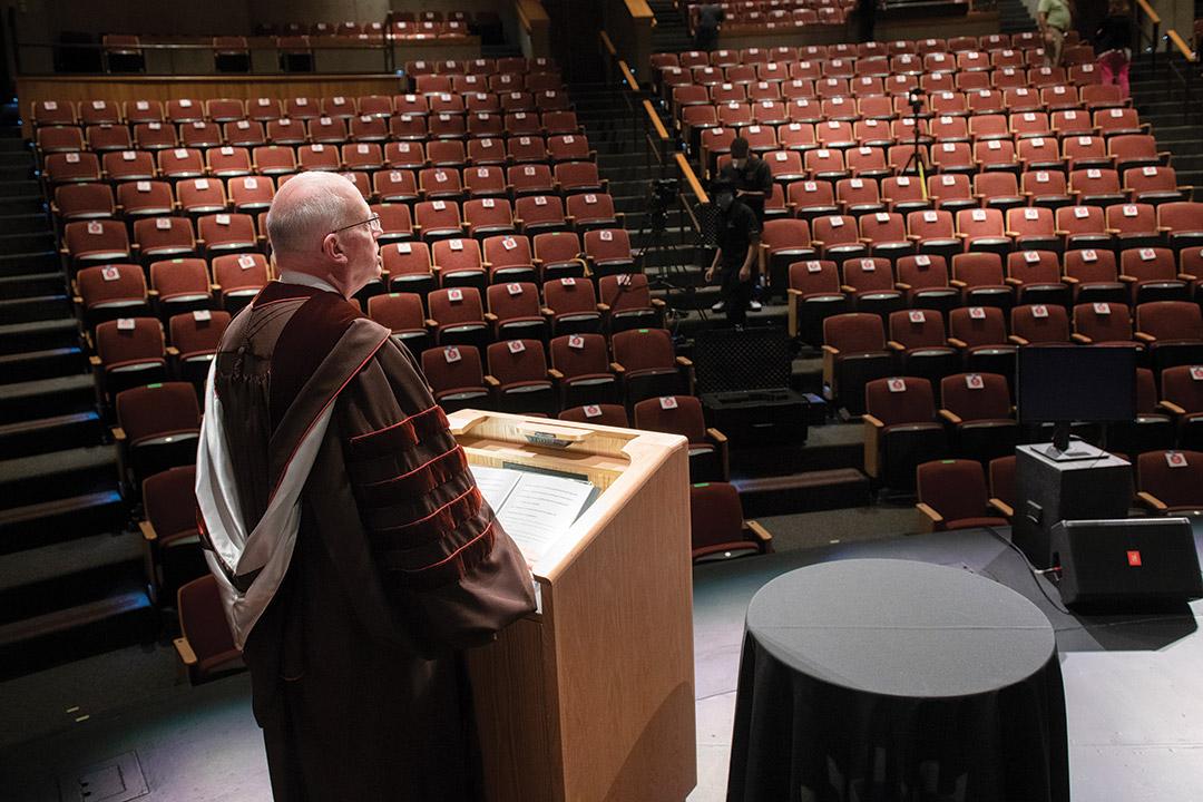 president David Munson speaking at podium to empty auditorium.