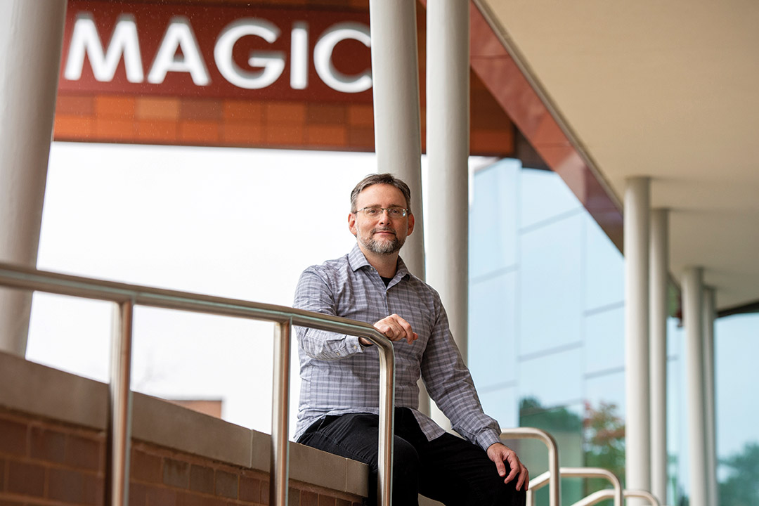 professor posing outside with building sign that says MAGIC in the background.