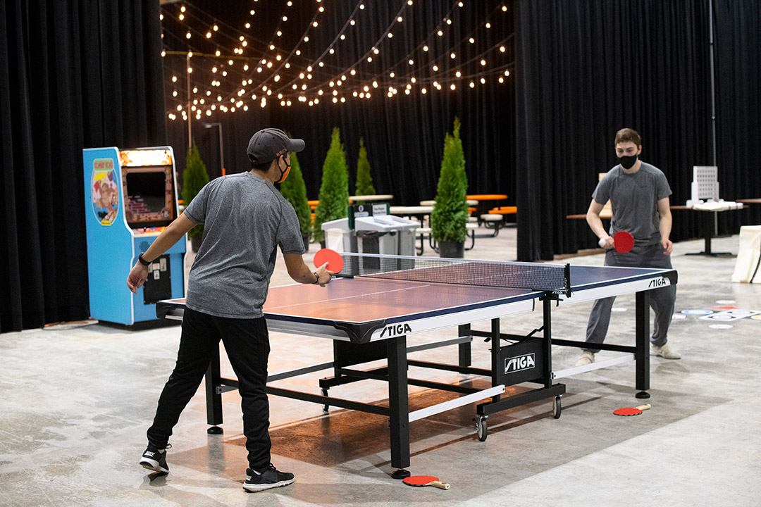 two students wearing face masks playing table tennis.