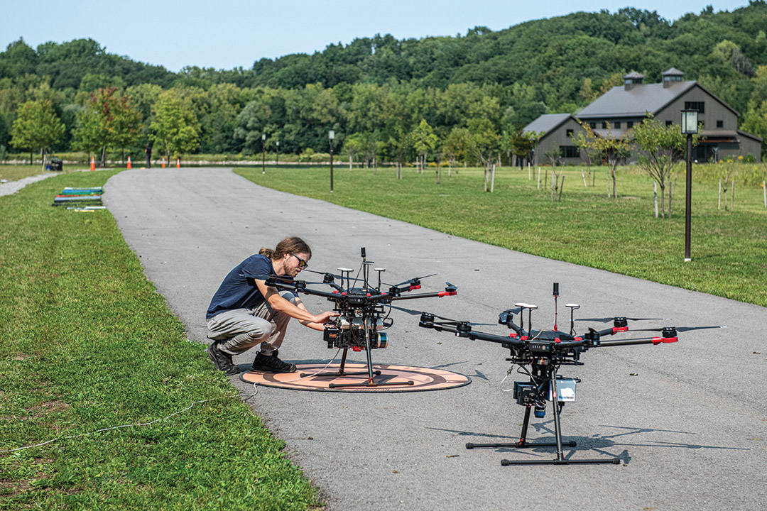 researcher setting up a drone on a roadway.