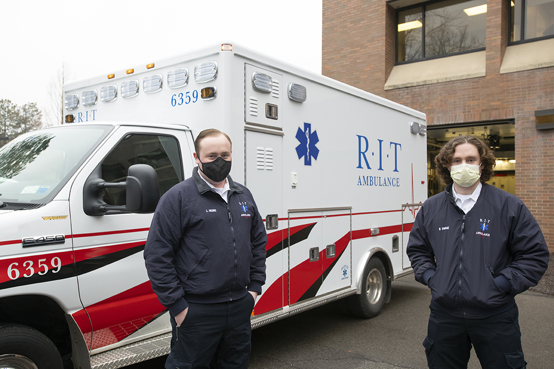 two masked members of RIT Ambulance in front of an ambulance