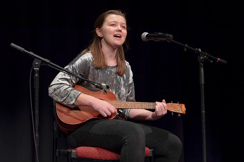 student playing guitar and singing into microphone.