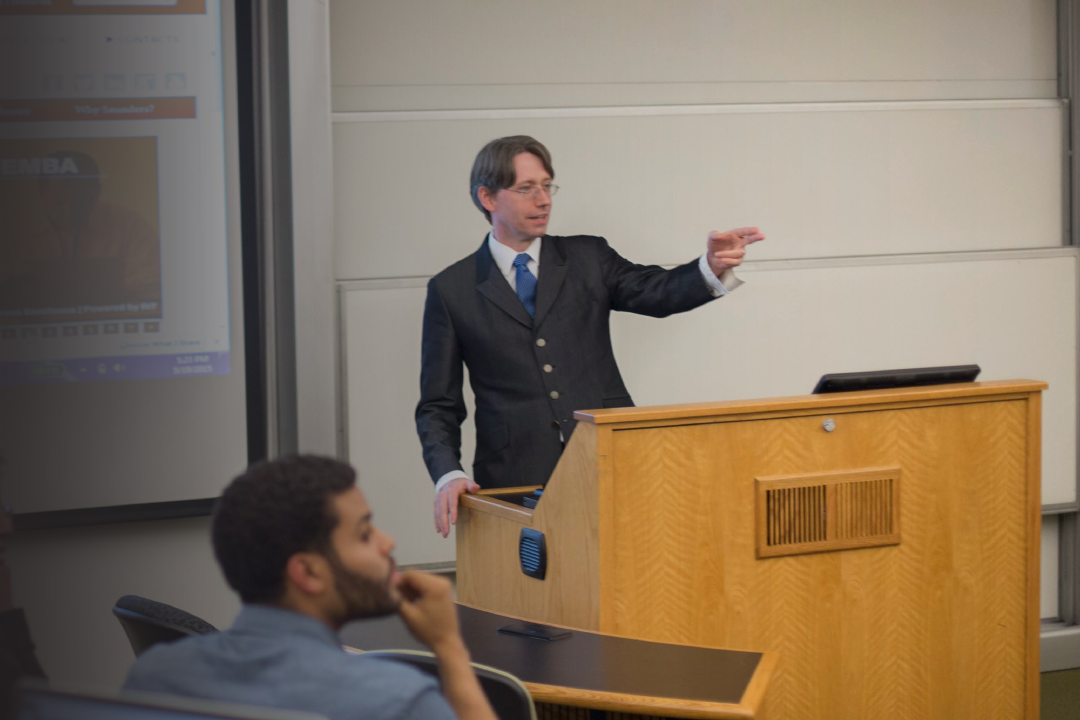 A Saunders professor teaches his class in a learning hall.