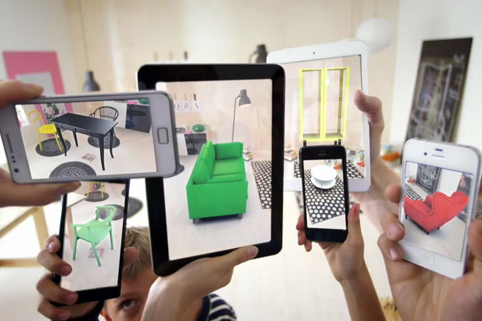 several smartphones and a tablet with an augmented reality app to display furniture in a room.