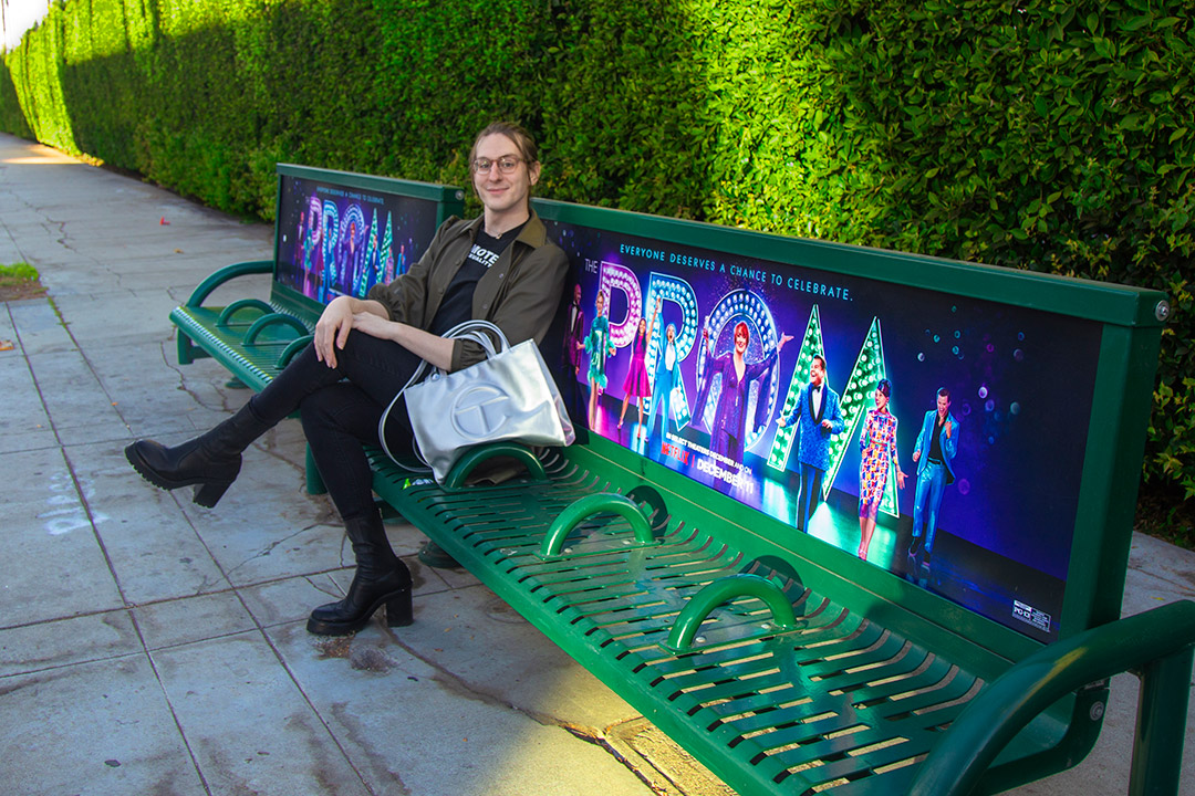 person sitting on a bench promoting the movie 'The Prom.'