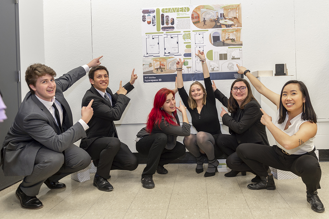 A group of smiling students point at their design concept that won the 2020 Hyperspace design challenge.