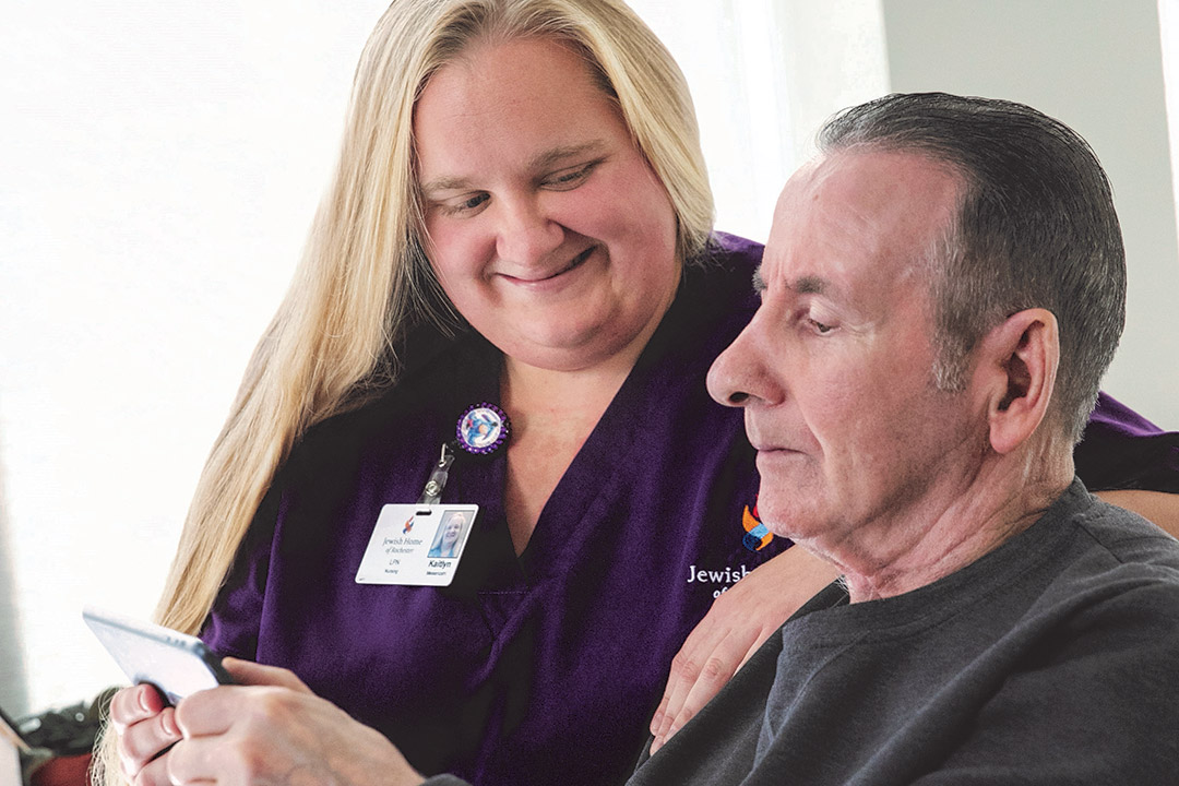 nurse helping a resident of a senior living facility use a smartphone.