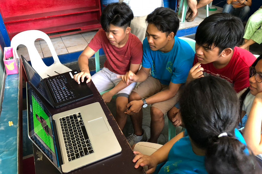 deaf children in the Philippines using laptop computers.