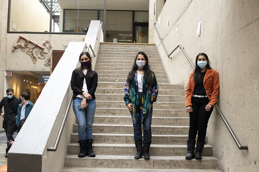 of three masked students standing posing for a photo in a stairway