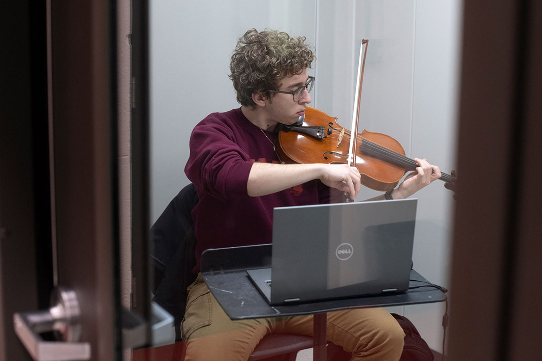 A student playing a viola, while sitting in front of a laptop.