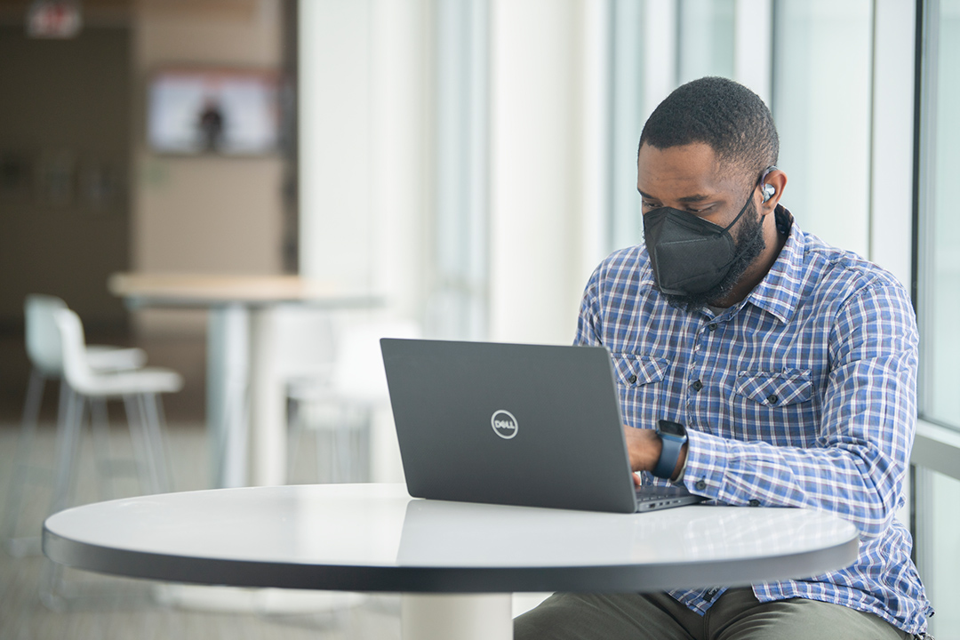 person wearing a hearing aid using a laptop computer.