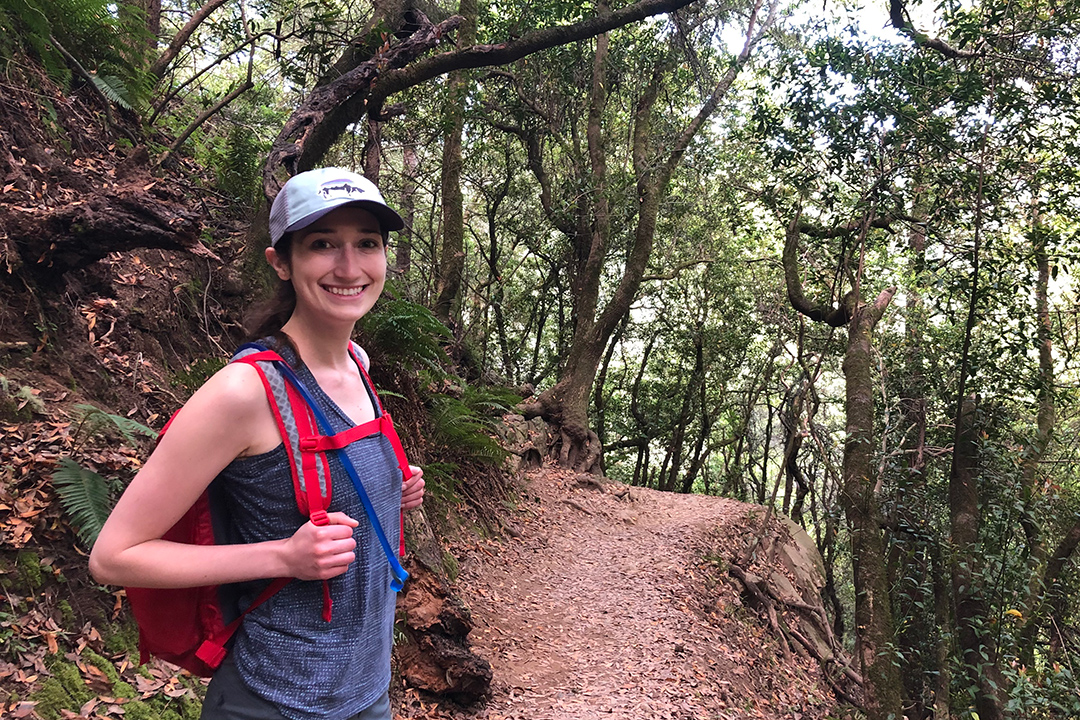 student hiking along wooded trail.
