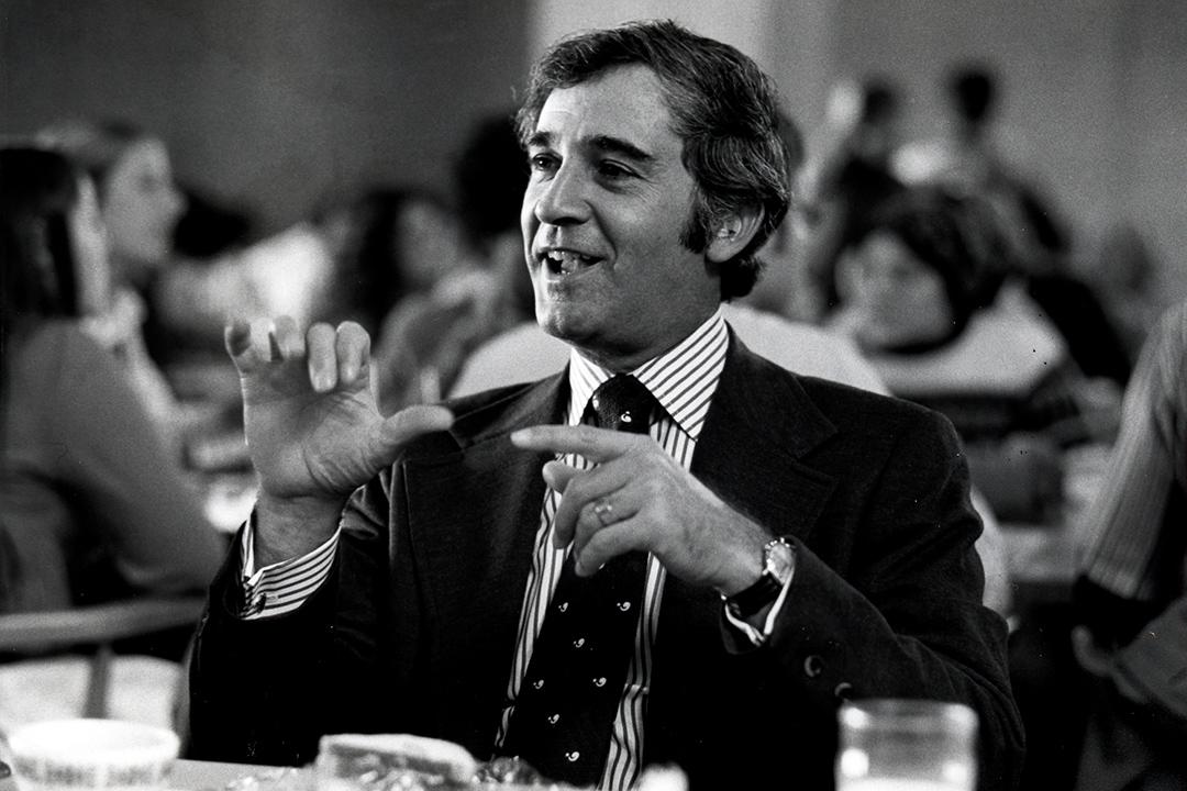 black and white photo of man using sign language.
