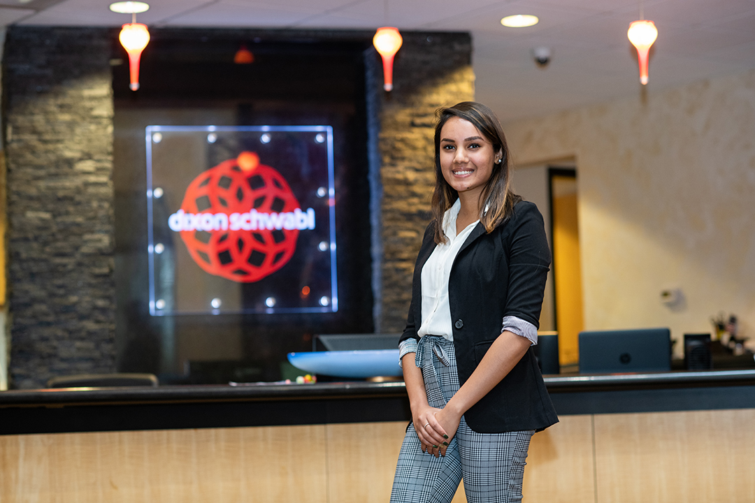Isha Mehta poses in front of a Dixon Schwabl sign at the agency's office.