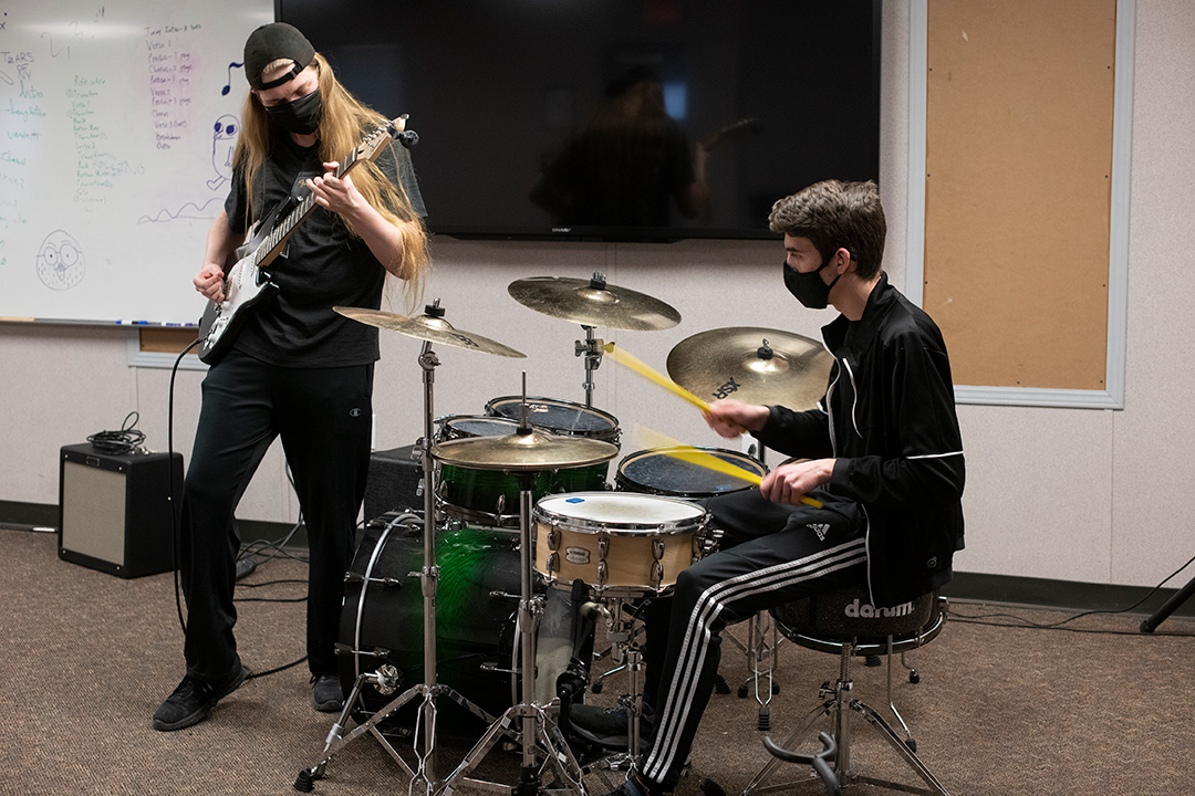 student playing the electric guitar next to student playing drums.