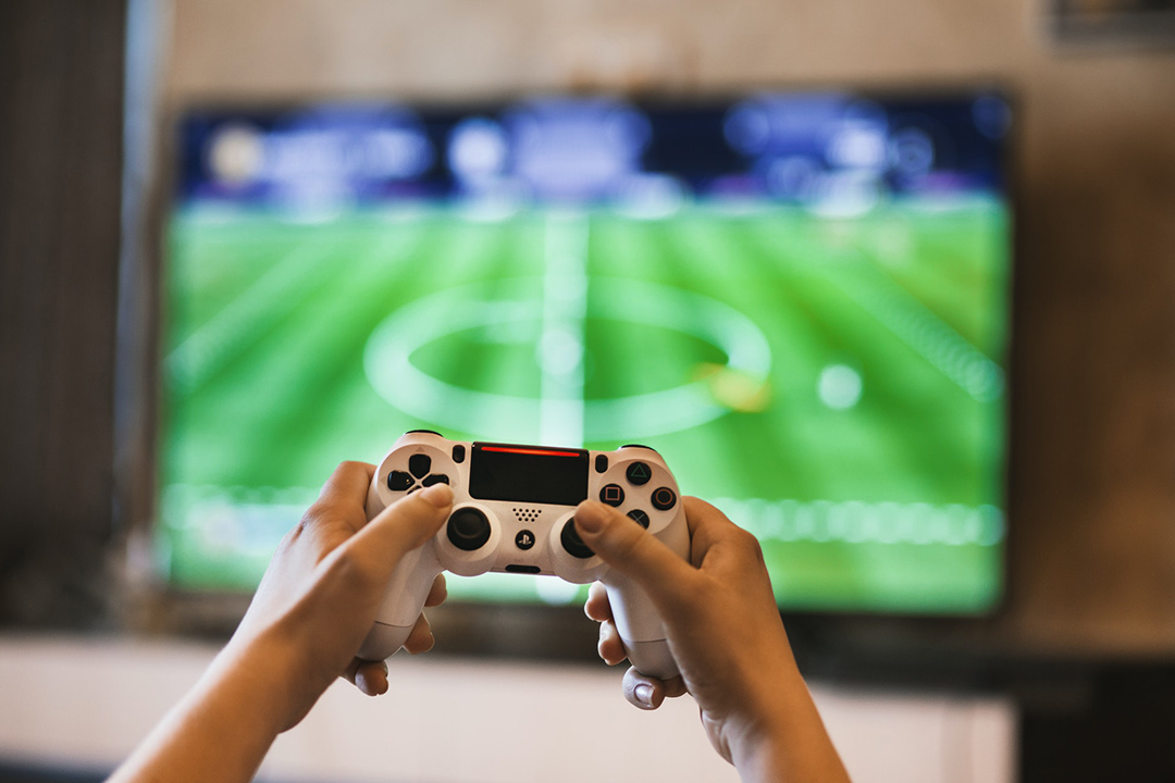user playing a sports game on a Playstation.