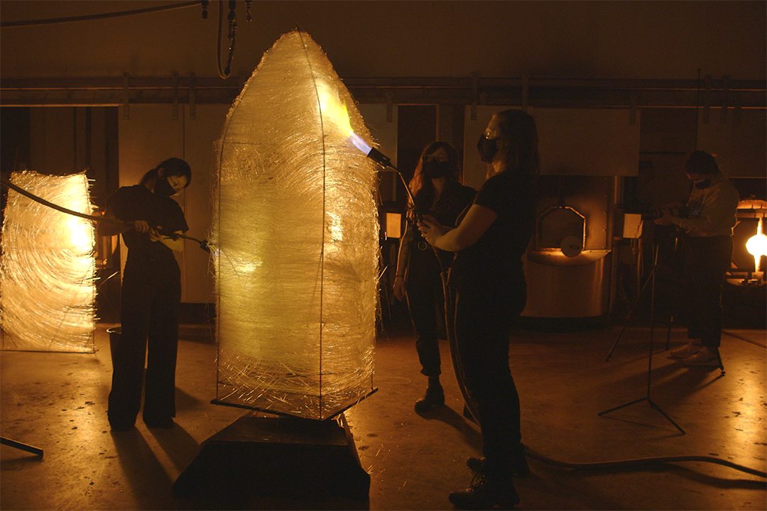 A group of artist take flame torches to a large, woven sculpture.