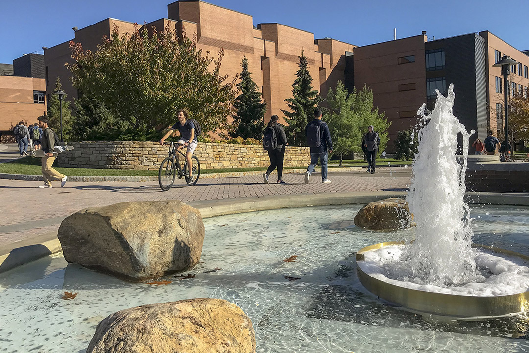 students walking and riding bikes outside near a fountain.