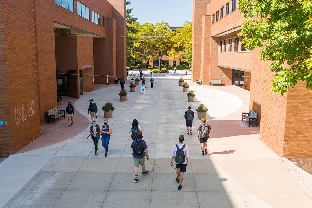 students walking outdoors between two brick buildings.