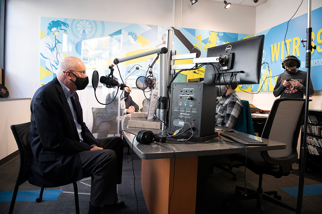 RIT President Munson wearing a mask and speaking into a microphone in a radio station.