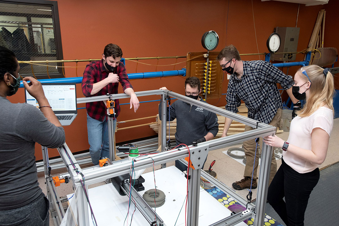 five students observing a 3D concrete printer.
