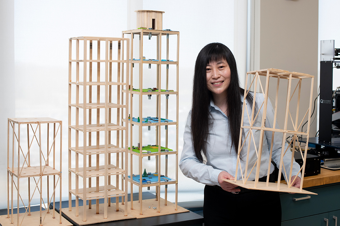 professor holding wooden models of skyscrapers.