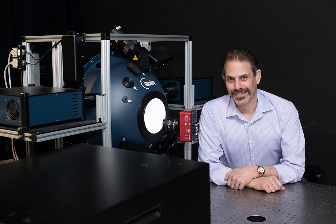 professor posing next to imaging equipment.