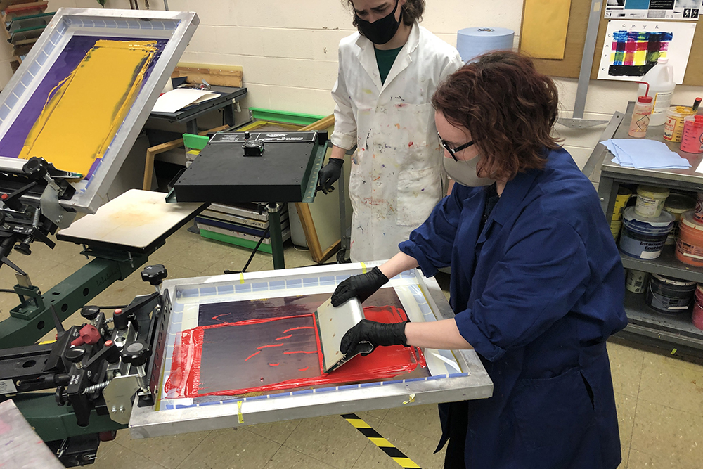 A student manipulates red ink during a screen-printing process.